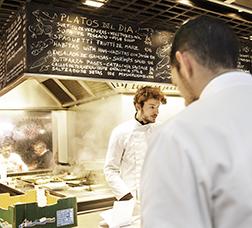 Cocinero trabajando en un puesto de un mercado alimentario