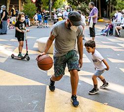 Hombre y niño jugando a baloncesto en la calle
