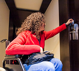 A woman in a wheelchair opening the door of a hotel room with a card.