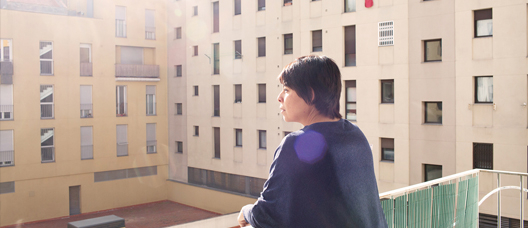 A woman on the balcony of an HPO flat