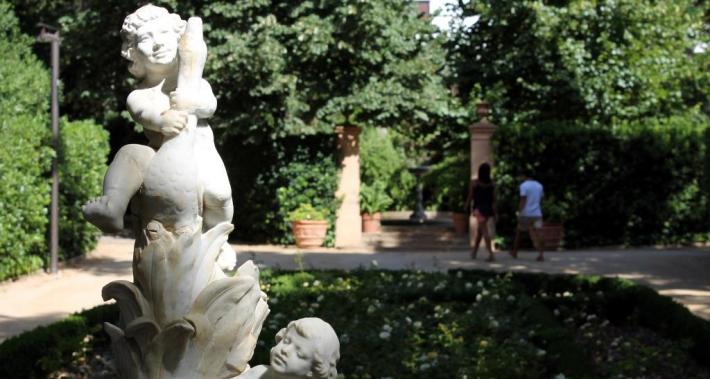 Escultura de piedra de dos ángeles y una pareja paseando por el parque