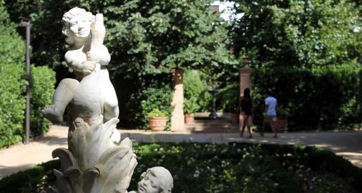 Escultura de pedra de dos àngels i una parella passejant pel parc