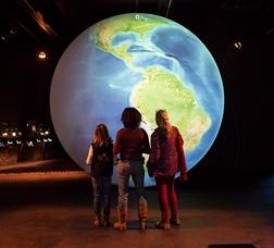 Tres persones observen un globus terraqüi al Museu de Ciències Naturals de Barcelona