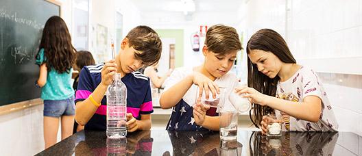 Un grupo de niñas y niños realiza un experimento en el laboratorio de un centro educativo