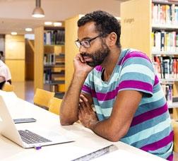 Un home seu davant d'un ordinador portàtil en una biblioteca