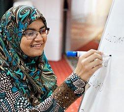 Una noia escriu en una pissarra