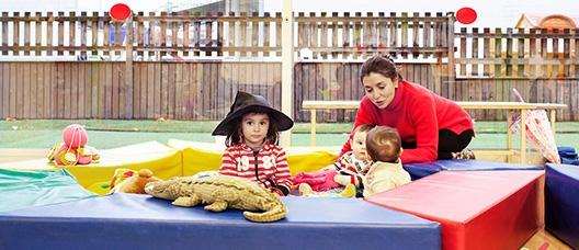 Grup de nens i nenes jugant amb ninots de peluix i amb una dona adulta