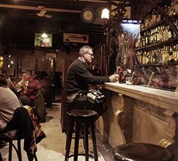 Home assegut a la barra d'un establiment de restauració prenent una consumició