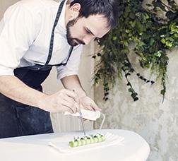 Cocinero adornando una tapa de comida antes de servirla