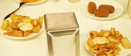 Platos de patatas bravas y croquetas en una mesa de un bar