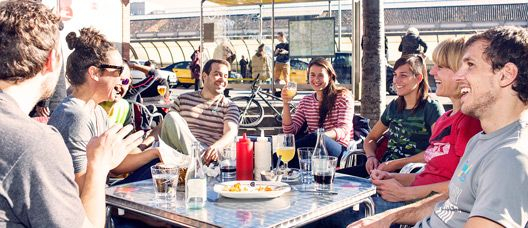 Group of young people laughing while they are seated on the terrace of a restaurant