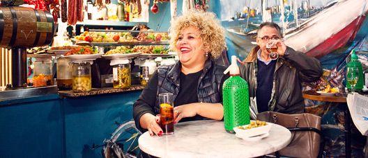 Dona asseguda a una taula d'una bodega prenent un vermut