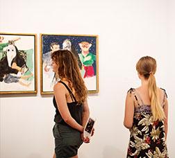 Niñas y jóvenes miran cuadros en un museo