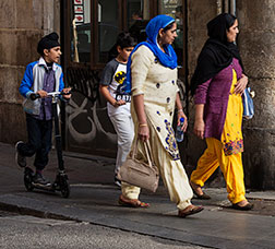 Two women and two children walking along a street