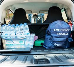 Vista del maletero abierto de un coche donde hay botellas de agua pequeñas y una mochila de emergencias sociales del Ayuntamiento de Barcelona.