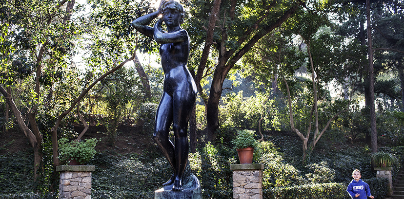 Estatua de una mujer en el parque de Laribal mientras un niño corre alrededor