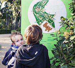 Dos menors mirant el mapa dels Jardins de Laribal