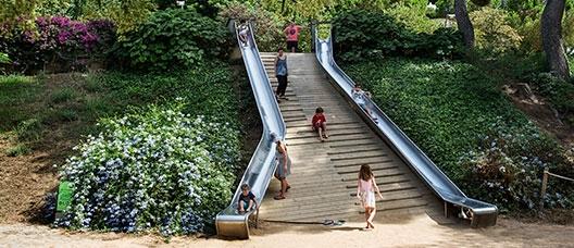 Niñas y niños bajan por toboganes en un parque