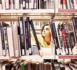 Una noia mira una prestatgeria plena de llibres en una biblioteca