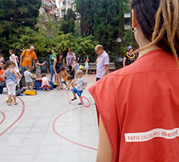 Una monitora atiende a los niños y niñas que juegan en el patio de una escuela