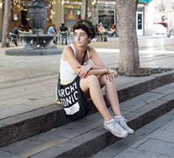 Una noia seu a les escales d'una plaça