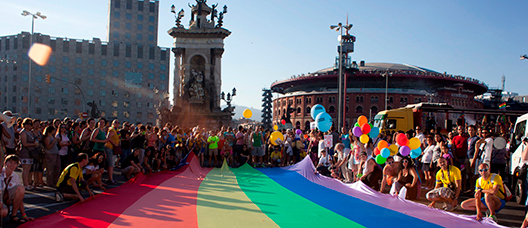 A group of people unfurling the gay flag at Plaça d'Espanya in Barcelona
