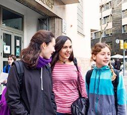 Grup de tres noies adolescents a la porta de l'institut