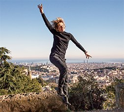 A woman jumping in a natural environment with Barcelona in the background