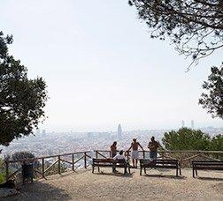 Un grup de persones descansa en un mirador des d'on es veu Barcelona amb el cel congestionat per la pol·lució