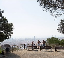 A group of people have a rest at a view point with a polluted Barcelona sky in the background