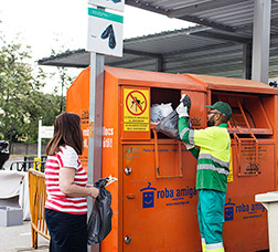 A recycling-centre worker helps someone who is bringing clothes to a recycling container.