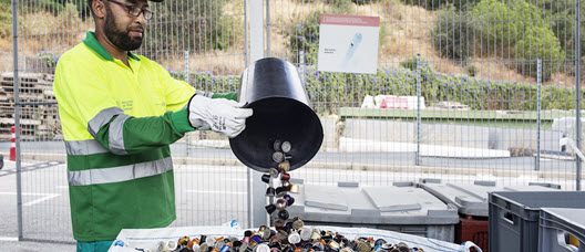 A recycling-centre worker classifies waste products.