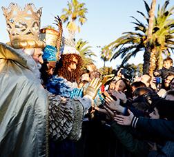 Los Reyes Magos saludan a unos niños en el Port Vell