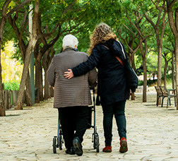 Photo of the backs of a young woman helping an elderly woman as they walk down an avenue, the elderly woman using a walking frame.