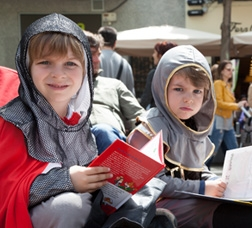 Two boys dressed as knights are sitting on the ground reading