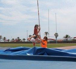 Una nena practica un salt d'alçada en un campus d'atletisme