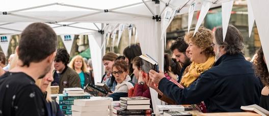 Personas miran libros en un puesto en la calle