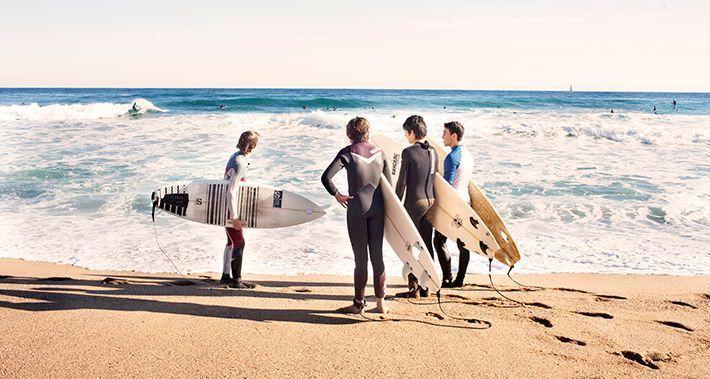 Grup de surfistes a la vora de l'aigua amb la taula de surf sota els braços