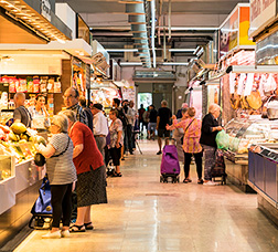 A market in Barcelona with people shopping at various food stalls.