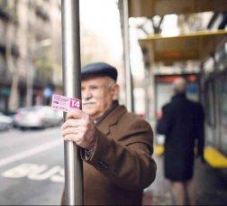 Hombre esperando el autobús en una parada mientras sostiene en la mano la Tarjeta Rosa