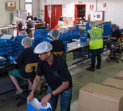 A group of people in an industrial building assembling cardboard boxes.