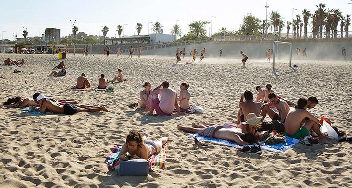Vista de la arena de una playa con grupos de personas tumbadas y grupos de personas que practican deportes