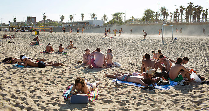 View of a sandy beach with groups of people laying on the sand and others playing sports