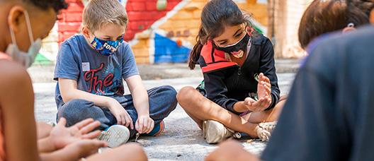 Un grup de nens en un casal miren quelcom que tenen entre les mans