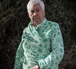 Una dona gran amb un batí verd davant d'uns arbusts