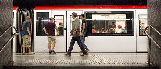 Metro station with a stationary train and people on the platform