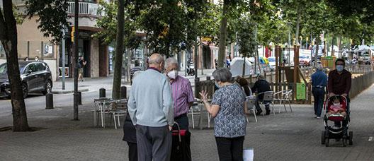 Un grup de persones grans conversa a peu dret a la via Júlia. Al voltant, es veuen comerços oberts i gent asseguda a les terrasses o passejant