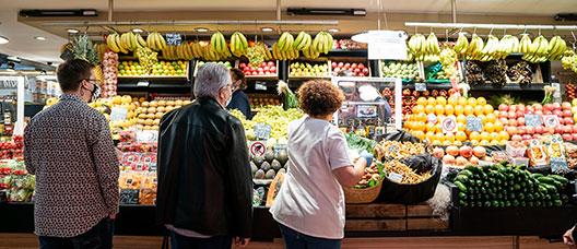 Gente comprando en una parada de frutas y verduras del Mercado del Ninot